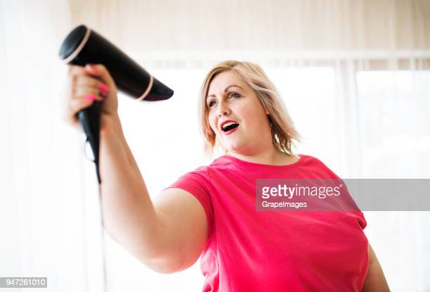 an attractive overweight woman with hair dryer at home, having fun. - big mike stock pictures, royalty-free photos & images