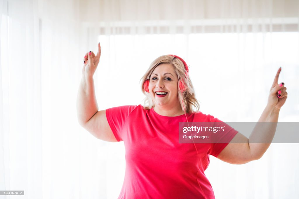 An attractive overweight woman with headphones at home, listening to music. : Stock Photo