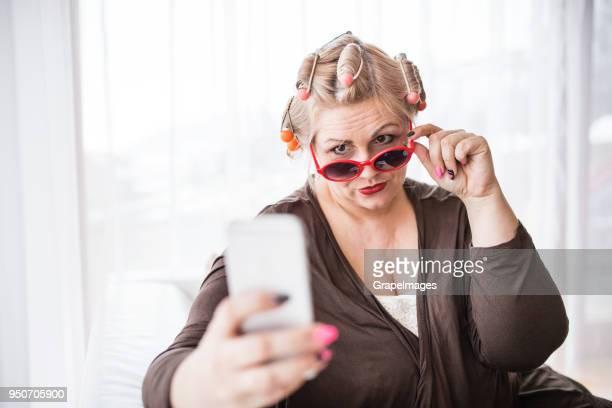 une séduisante femme en surpoids avec lunettes de soleil et les bigoudis à la maison, prenant selfie. - big fat white women photos et images de collection