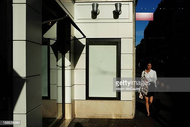 An attractive woman dressed in black and white walks past a black and white building in central Geneva. The late afternoon light is sharp and the...