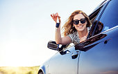 An attractive woman in a car holds a car key in her hand