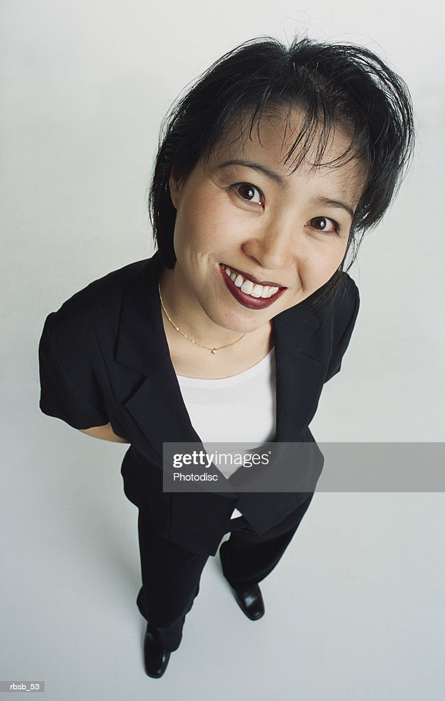 an attractive young asian woman with short dark hair dressed in a dark suit and white shirt is looking up into the camera with her hands behind her back : Foto de stock