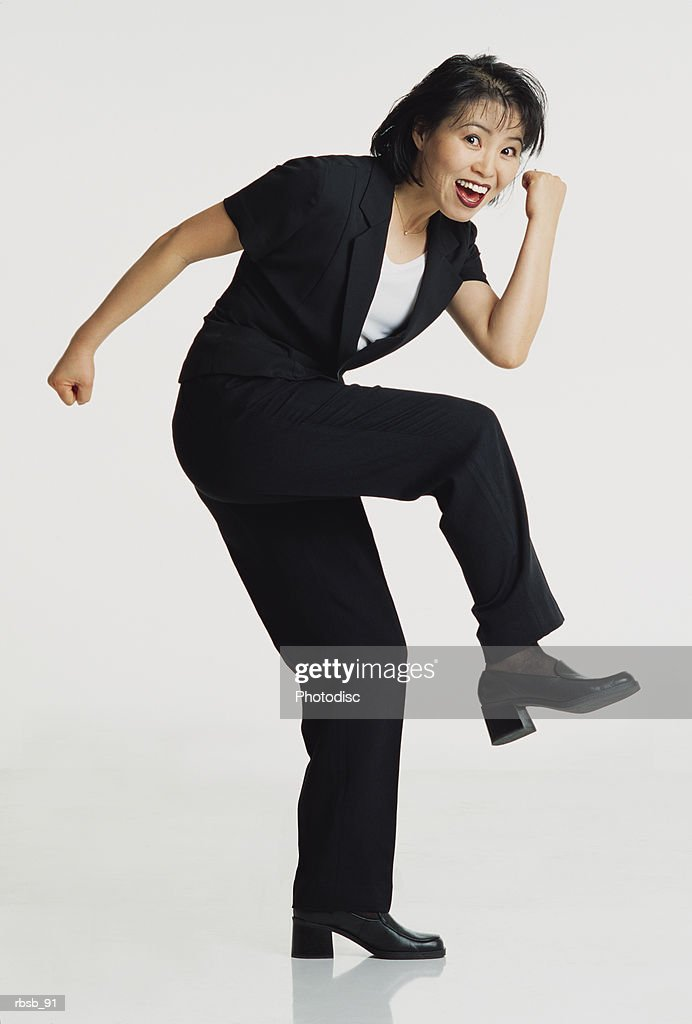 an attractive young asian woman with short dark hair looking into the camera with her arms and knee raised in a celebratory gesture : Stockfoto