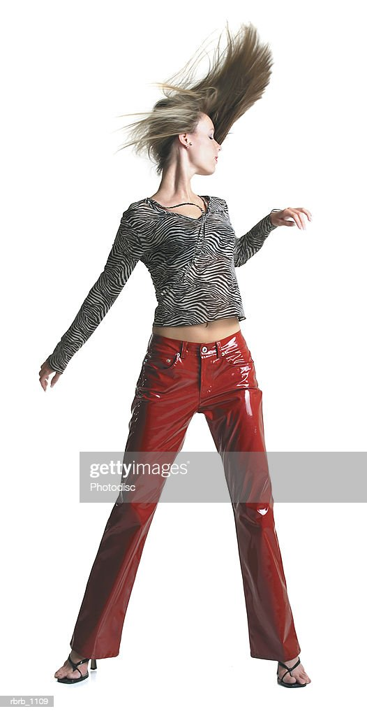 an attractive young blonde woman in red pants dances wildly and tosses her hair to the side : Stockfoto