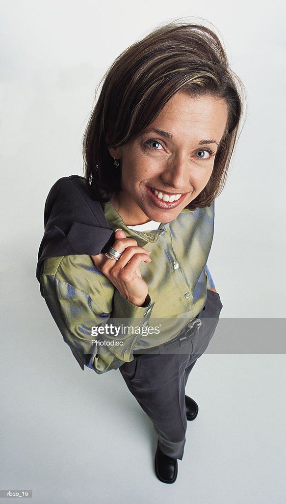 an attractive young caucasian woman with blue eyes and shoulder length brown hair in a green shirt and and grey pants stands looking into the camera : Foto de stock
