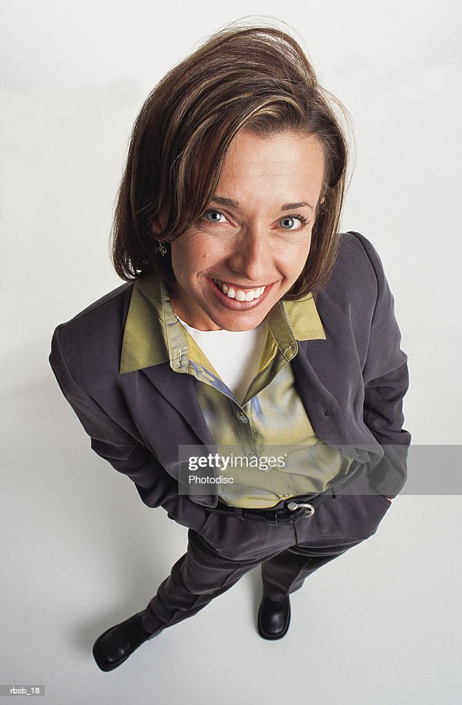 an attractive young caucasian woman with blue eyes and shoulder length brown hair in a grey suit and green shirt stands smiling and looking up into the camera : Foto de stock