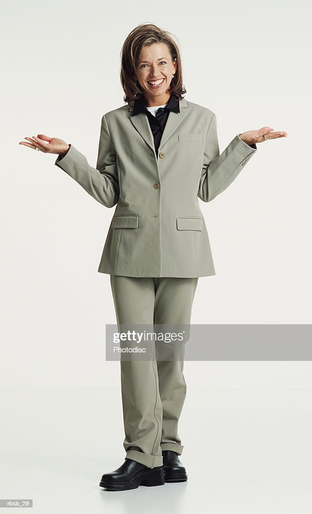 an attractive young caucasian woman with blue eyes and shoulder length brown hair in a green shirt and and grey pants stands looking into the camera with her hands up in a shrugging gesture : Stockfoto