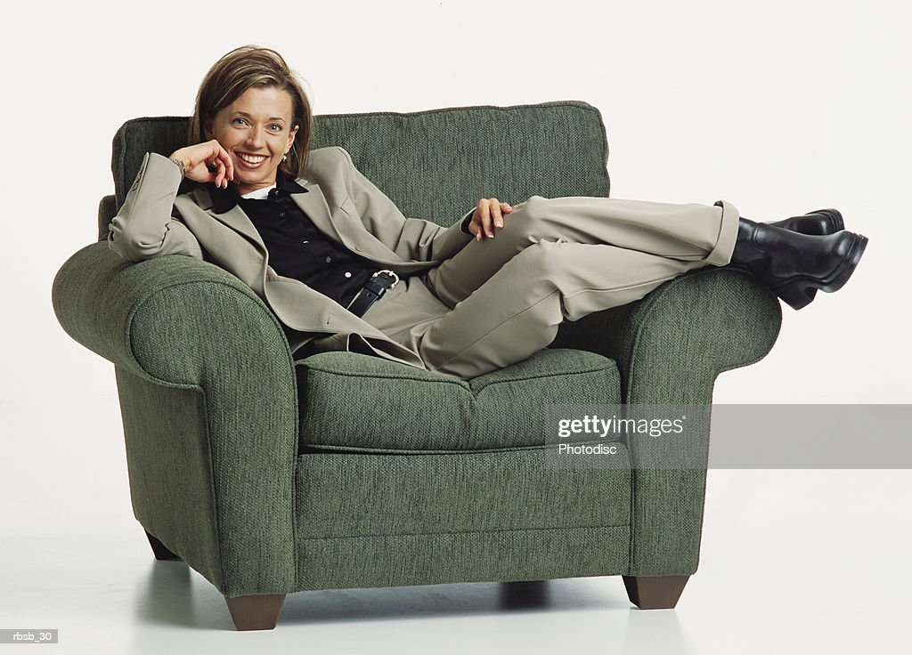 an attractive young caucasian woman with blue eyes and shoulder length brown hair in a green shirt and and grey pants reclines across a green easy chair looking into the camera : Foto de stock