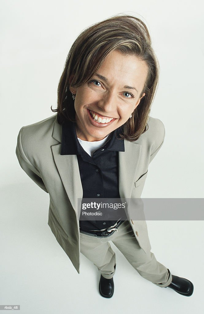 an attractive young caucasian woman with blue eyes and shoulder length brown hair in a light suit and black shirt stands smiling and looking up into the camera : Foto de stock