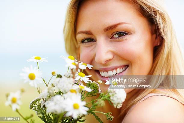An attractive young female with fresh flowers smiling