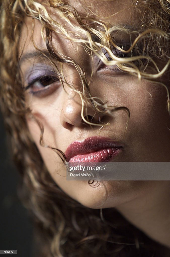 an attractive young hispanic woman pouts into the camera as her hair is tossed in front of her face : Stockfoto