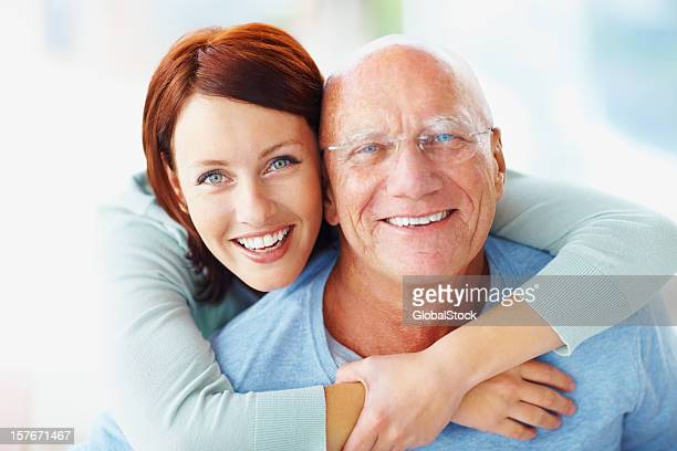 an attractive young woman embracing her grandfather from back - old man young woman stock photos and pictures