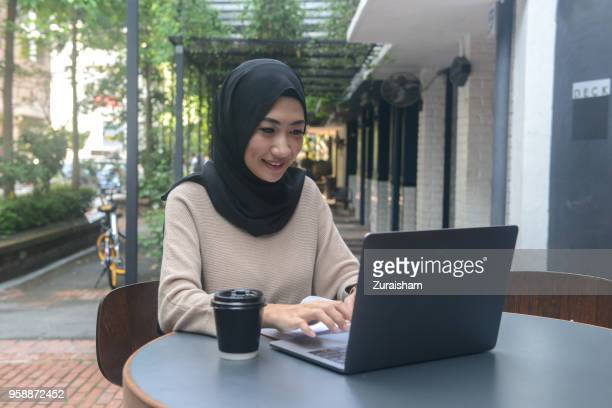 an attractive young woman wearing hijab using a computer laptop in a cafe - zurückhaltende kleidung stock-fotos und bilder
