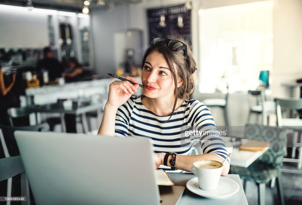 An attractive young woman with laptop and a cup of coffee sitting in a cafe, writing. : Stock Photo