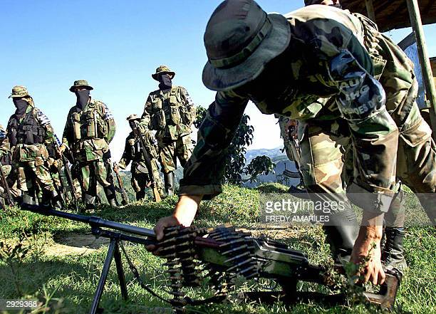 An AUC paramilitary fighter of the Heroes of Granada Bloc lays down his light machinegun 04 february 2004 in the mountainous Antioquia sector...