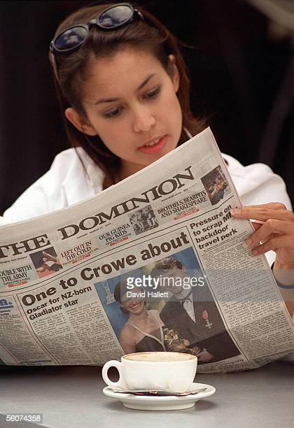 An Auckland office worker takes a break in a city cafe with todays paper featuring the front page story about Russell Crowe's Oscar win with the head...