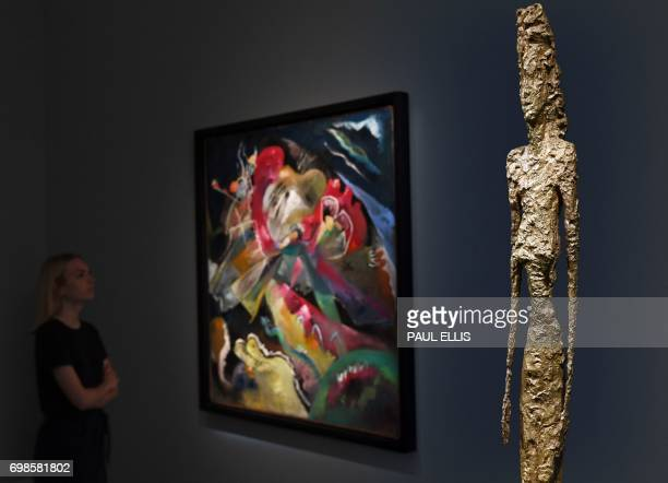 An auction house employee looks at Russian painter Wassily Kandinsky's oil painting 'Bild mit weissen Linien' as Swiss artist Alberto Giacometti's...
