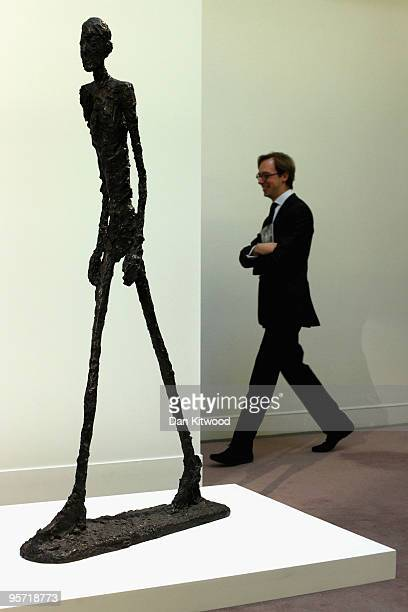An auction house employee walks past a work entitled 'Homme qui marche' by Alberto Giacometti at Sotheby's auction house on January 12 2010 in London...