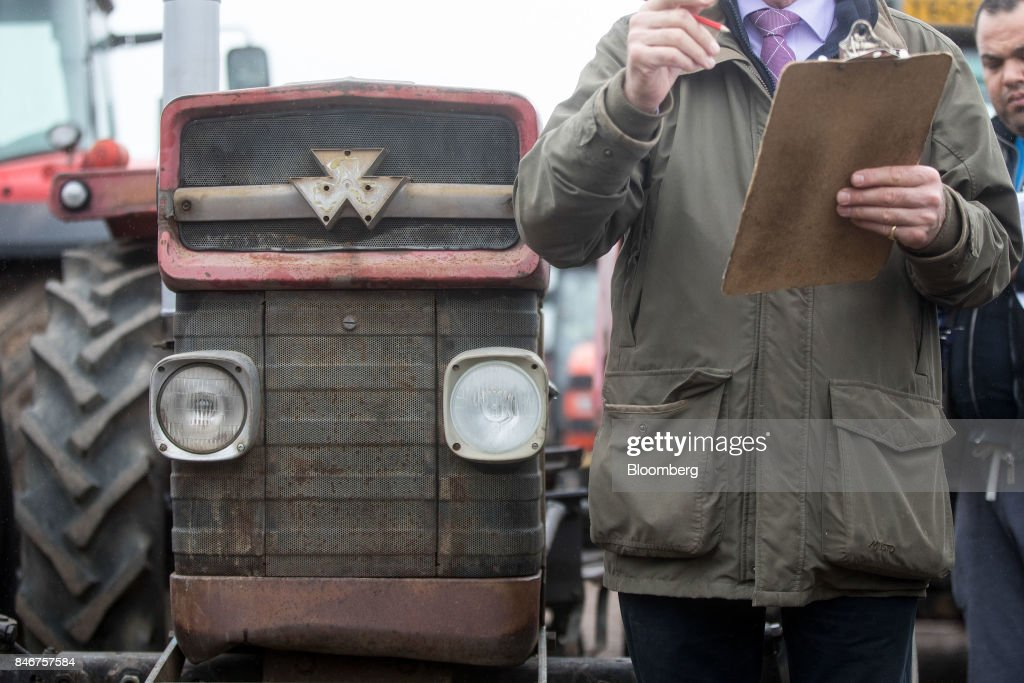 An auctioneer checks his clipboard for information as he stands in front of a tractor manufactured by Massey Ferguson Corp. at the Cheffins Cambridge Machinery Sales monthly machinery and plant auction in Sutton, U.K., on Monday, Sept. 4, 2017. The debate over food andfarmingpolicy after Brexit has heated up recently, with Environment Secretary Michael Gove telling BBC Radio 4 that the U.K wouldnt lower its animal welfare or environmental standards to achieve any new trade deals. Photographer: Simon Dawson/Bloomberg via Getty Images