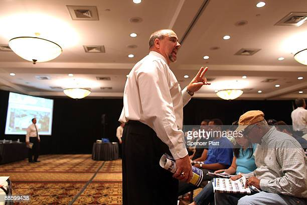 An auctioneer from Hudson Marshall takes bids during a auction for more than 25 forclosed homes at the Renaissance Newark Airport Hotel on June 20...