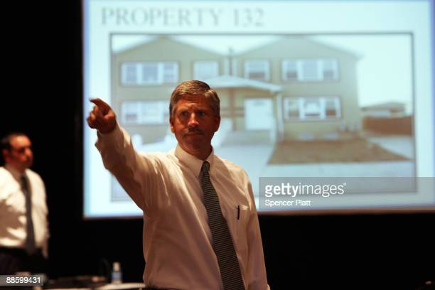 An auctioneer from Hudson Marshall takes bids during an auction for more than 25 foreclosed homes at the Renaissance Newark Airport Hotel on June 20...