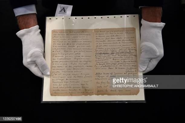 An auctioneer holds a letter cowritten by Dutch painter Vincent Van Gogh and French painter Paul Gauguin on the eve of its auction sale at Drouot...