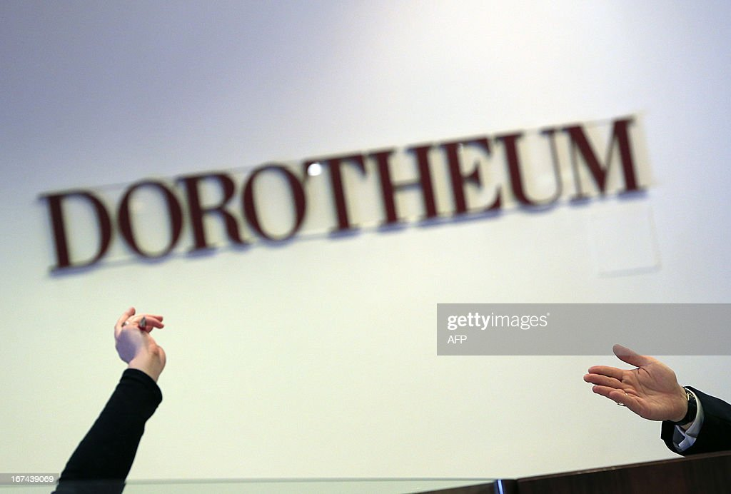 An auctioner (R) and a bidder gesture during the bid for a lock of hair from Emperor Franz Joseph I of Austria as part of an auction of Imperial Court Memorabilia and Historical Objects at the Palais Dorotheum auction house in Vienna on April 25, 2013. The lock of hair was sold for 11,000Euros.