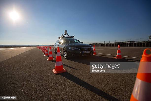 An Audi A6 diesel automobile produced by Volkswagen AG passes drives between road traffic cones during an automated driving exercise on a test track...
