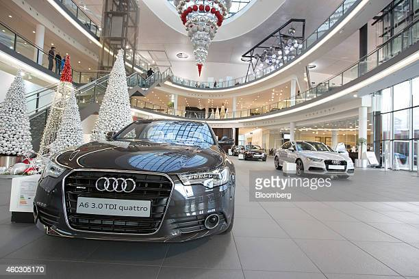 An Audi A6 TDI Quattro automobile left and other of Audi AG models sit on display as festive treeshaped decorations stand in the Audi Forum in...