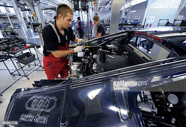 An Audi AG employee assembles the engine of an Audi R8 automobile on the production line at the company's factory in Neckarsulm Germany on Wednesday...