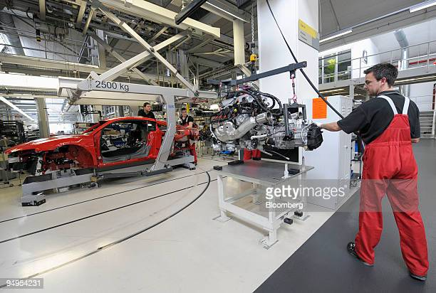 An Audi AG employee moves the engine of an Audi R8 automobile on the production line at the company's factory in Neckarsulm, Germany, on Wednesday,...