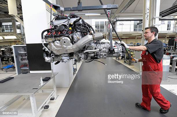 An Audi AG employee moves the engine of an Audi R8 automobile on the production line at the company's factory in Neckarsulm Germany on Wednesday May...
