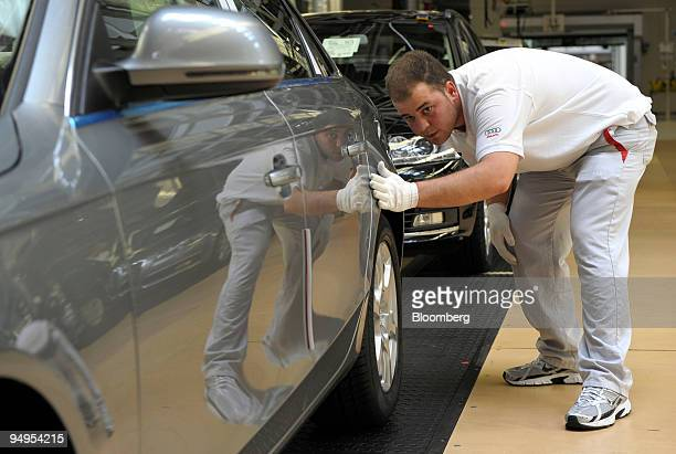 An Audi AG employee performs a final check on an Audi A4 automobile on the assembly line at the company's factory in Neckarsulm Germany on Wednesday...