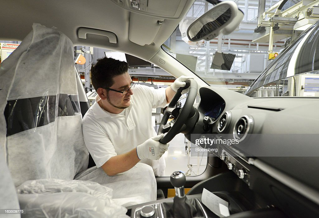 An Audi employee fits a steering wheel inside an Audi A3 automobile, produced by Volkswagen AG's Audi brand, as it moves along the production line at the company's plant in Ingolstadt, Germany, on Monday, March 11, 2013. Audi, the world's second-largest maker of luxury vehicles, plans to spend 13 billion euros ($17 billion) through 2016 to develop new cars and expand production capacity as it pursues Bayerische Motoren Werke AG's sales lead. Photographer: Guenter Schiffmann/Bloomberg via Getty Images