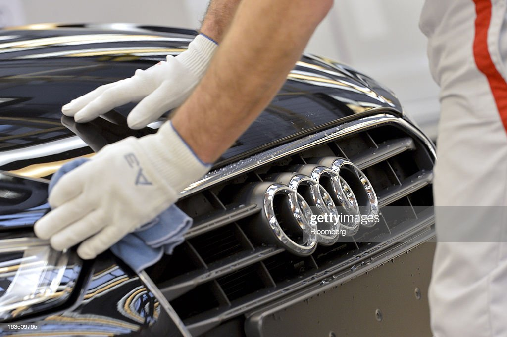 An Audi employee polishes the hood of an Audi A3 automobile, produced by Volkswagen AG's Audi brand, as it moves along the production line at the company's plant in Ingolstadt, Germany, on Monday, March 11, 2013. Audi, the world's second-largest maker of luxury vehicles, plans to spend 13 billion euros ($17 billion) through 2016 to develop new cars and expand production capacity as it pursues Bayerische Motoren Werke AG's sales lead. Photographer: Guenter Schiffmann/Bloomberg via Getty Images
