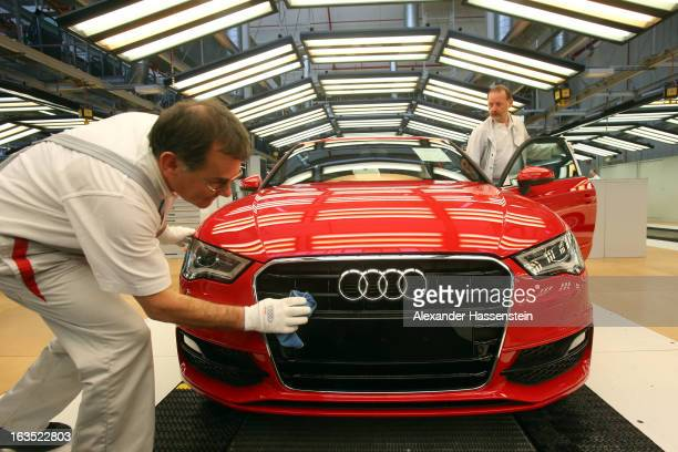 An Audi employee polishes the hood of an Audi A3 automobile, produced by Volkswagen AG's Audi brand, as it moves along the production line at the...