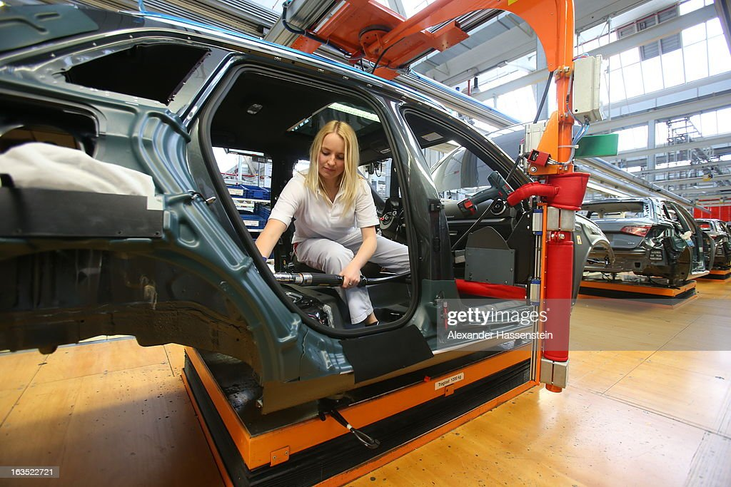 An Audi employee works on the interior of an Audi A3 automobile, produced by Volkswagen AG's Audi brand, as the vehicle moves along the production line at the company's plant in Ingolstadt, Germany, on Monday, March 11, 2013. Audi is set to spend 13 billion euros ($17 billion) through 2016 to expand and develop new cars pursuing BMW?s sales lead.