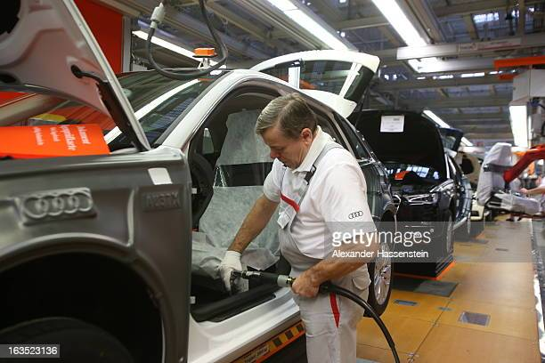 An Audi employee works on the interior of an Audi A3 automobile, produced by Volkswagen AG's Audi brand, as the vehicle moves along the production...
