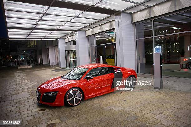 An Audi R8 etron electric automobile manufactured by Volkswagen AG sits connected to a charging station outside the Audi AG forum in Ingolstadt...