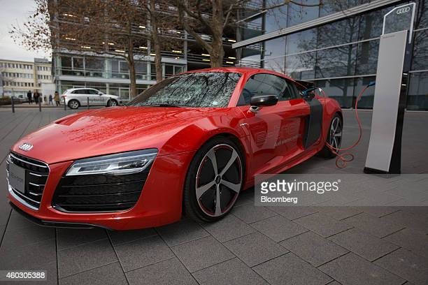 An Audi R8 etron hybrid automobile sits connected to an electric charging station outside the Audi AG Forum in Neckarsulm Germany on Wednesday Dec 10...