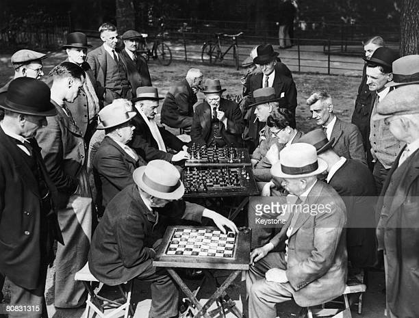 An audience gathers for a meeting of the Clapham Common Open Air Chess and Draughts Club who play every afternoon circa 1920
