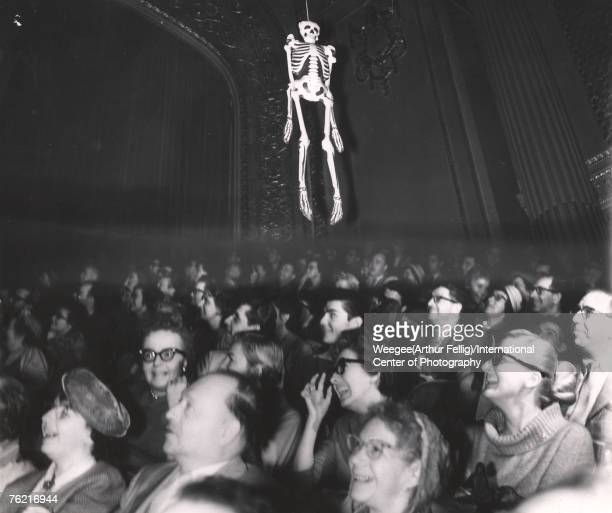 An audience laughs as an inflatable skeleton hangs over their heads, late 1950s or early 1960s. They are probably in a movie theatre during a screen...