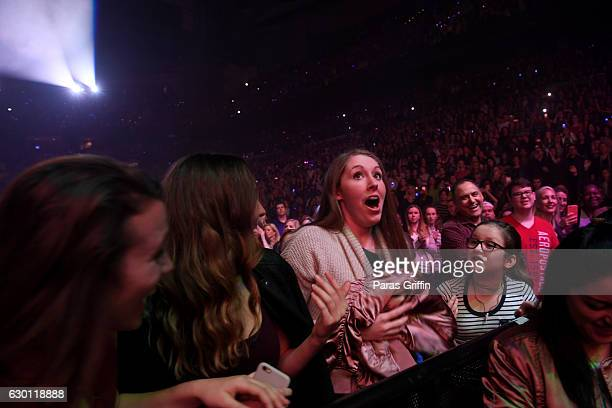 An audience member catches a jacket as Fifth Harmony performs onstage during Power 961's Jingle Ball 2016 at Philips Arena on December 16 2016 in...