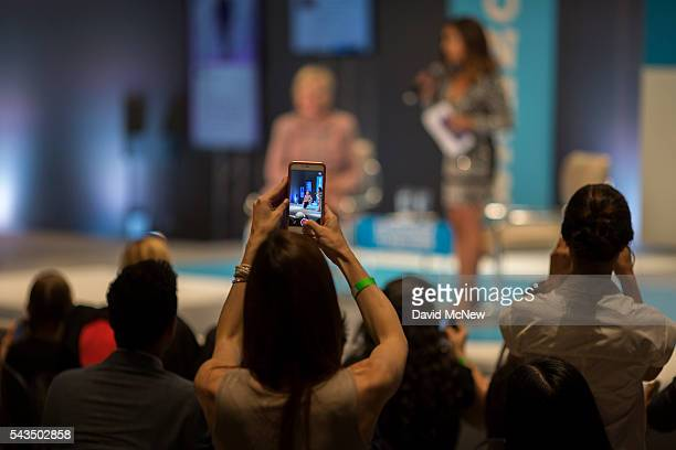 An audience member photographs Democratic presidential candidate Hillary Clinton at a town hall discussion with digital content creators at Neuehouse...