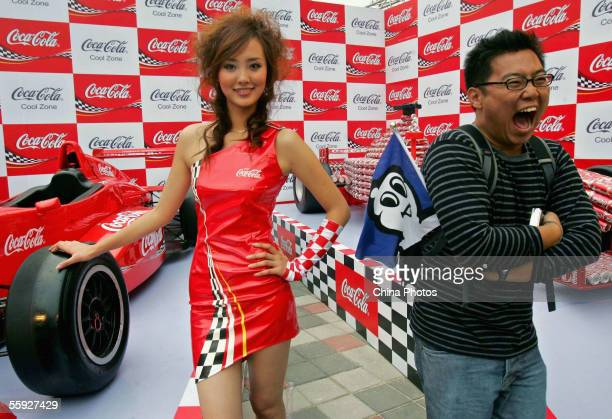 An audience member poses for pictures with a model during the Chinese F1 Grand Prix at the Shanghai International Circuit on October 14 2005 in...