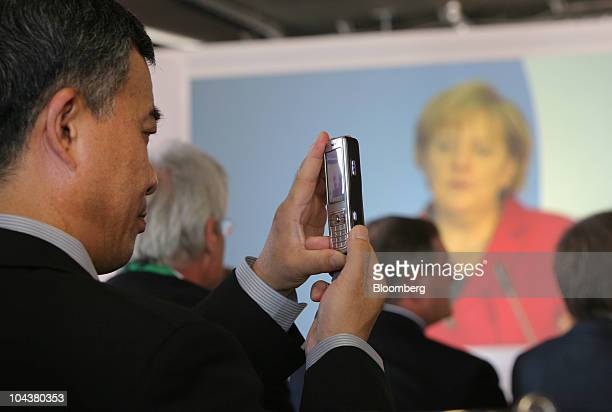 An audience member takes a mobile phone camera picture of Angela Merkel Germany's chancellor speaking at the Merck KGaA research center in Darmstadt...
