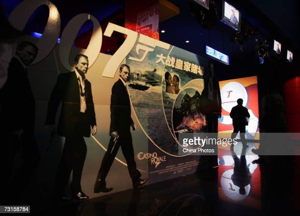 An audience member walks past a billboard for Casino Royale which officially debuts in China today January 30 2007 in Wuhan of Hubei Province China