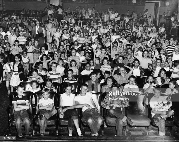 An audience of mostly children cheer and make faces in a movie theater mid 1950s