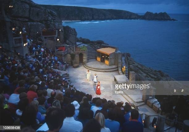 An audience watch a performance at the open air Minack Theatre on the coast of Porthcurno Penzance Cornwall circa 1984