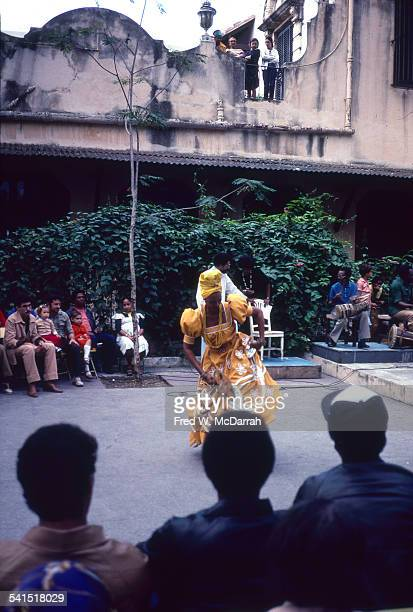 An audience watches as an unidentified woman in an elaborate yellow dress and headdress dances in Plaza Vieja to a live band Havana Cuba January 28...